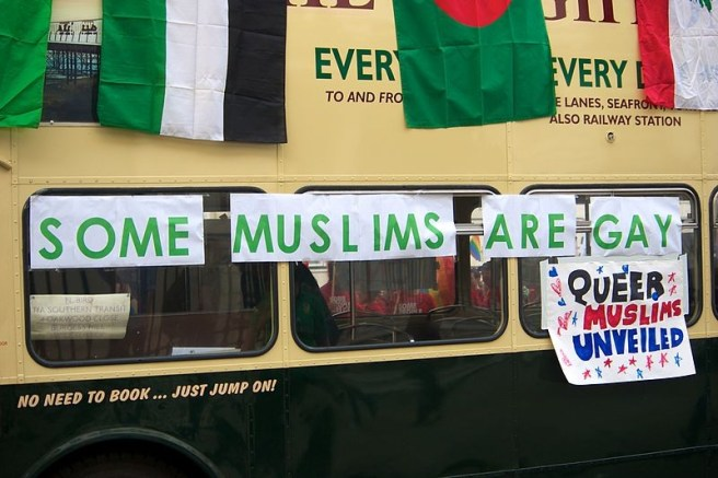 """picture of a bus with protest signs that read """"Queer Muslims United"""""""
