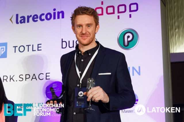 Luke Lombe from the PlayChip ICO team collecting the San Francisco Blockchain Economic Forum ICO Pitch 'Draper Hero's Choice Award'.