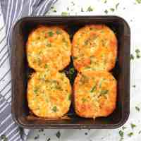 Four pieces of garlic bread in a baking tin garnished with herbs