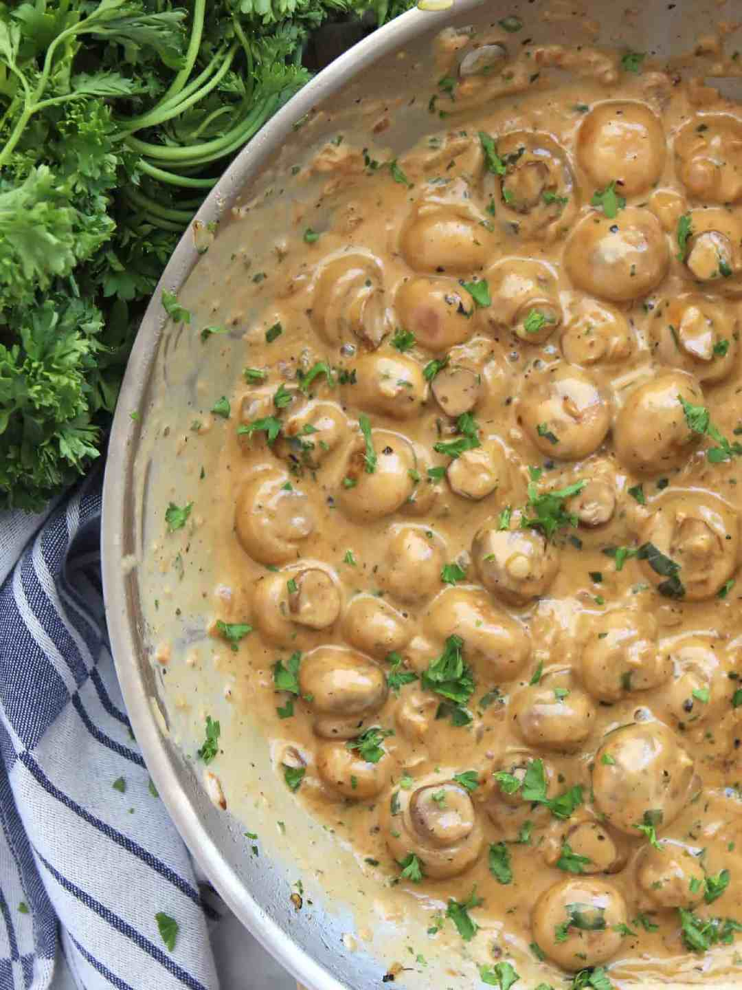 Creamy garlic mushrooms in a skillet next to a bunch of fresh herbs