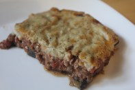 A layer of eggplants and onions, topped with a layer of ground meat, topped with a layer of baked béchamel sauce.