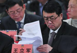Deputy Mayor of Chongqing Wang reads documents as he attends a session of CPPCC of the Chongqing Municipal Committee, in Chongqing municipality