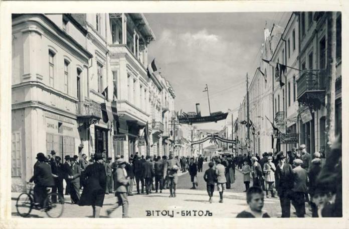 """Неделна глетка на главната улица во 1939 година. Живописно украсената улица и големиот број на граѓани даваат слика на динамичен град. Над улицата се транспарентите со порака """"Чувајмо наше море"""" на бродот """"Живела Југославија"""" на тробојната трака, и Стовариште Битољске Текстилне Индустрије А.Д. на крајот на улицата. Фурната Паско носи име: Пекарница Крагујевац Диме Н. Петровиќ, следат Сингер шивачки машини, и Охрид на левата страна, берберницата """"Здравље"""", берберницата кај Круме и автобуската станица на десната страна."""