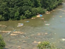 """People on rafts """"shooting the hootch"""" rapids."""