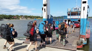 travellers boarding a small car ferry. The weather is fine with blue sky. The travelers are carrying heavy back packs.