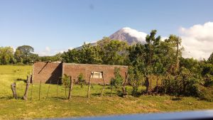 View of Volcano Concepcion with cloud rolling down its flanks. Agricultural building in the field in the foreground, blue sky.