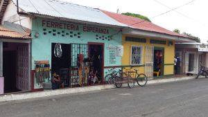 street and buildings in Moyogalpa.  The buidlings are painted blue and yellow, young men sitting in the doorways of the shops, bicycles propped up outside