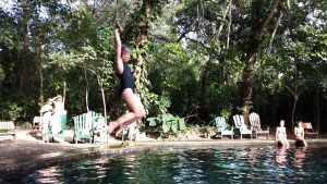 woman swinging into natural mineral pool on rope swing.