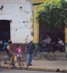 Street in Rivas, bicycles propped against the kerb, woman, child and man in the foreground talking, two men sitting in the doorway to a house one sewing on a treadle sewing machine