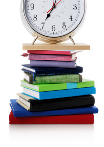 a big alarm clock on top of a pile of books and agendas