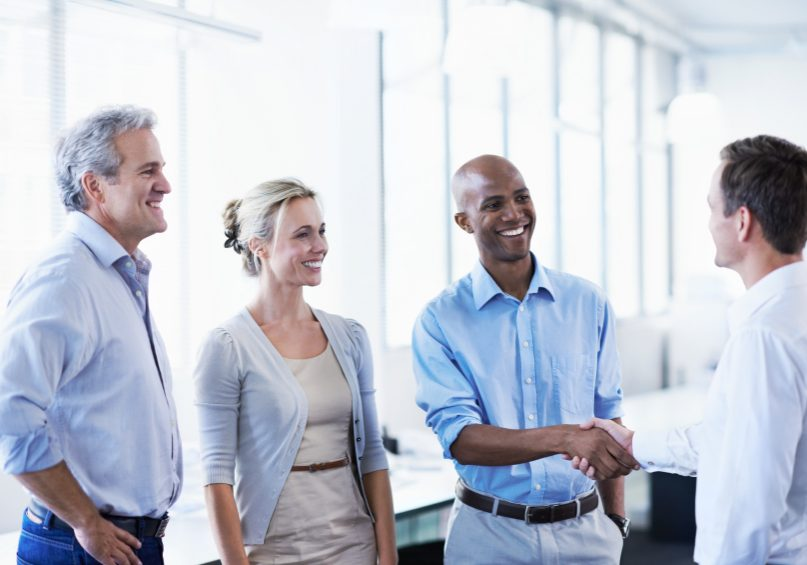 Shot of a diverse group of coworkers shaking hands and talking in an office