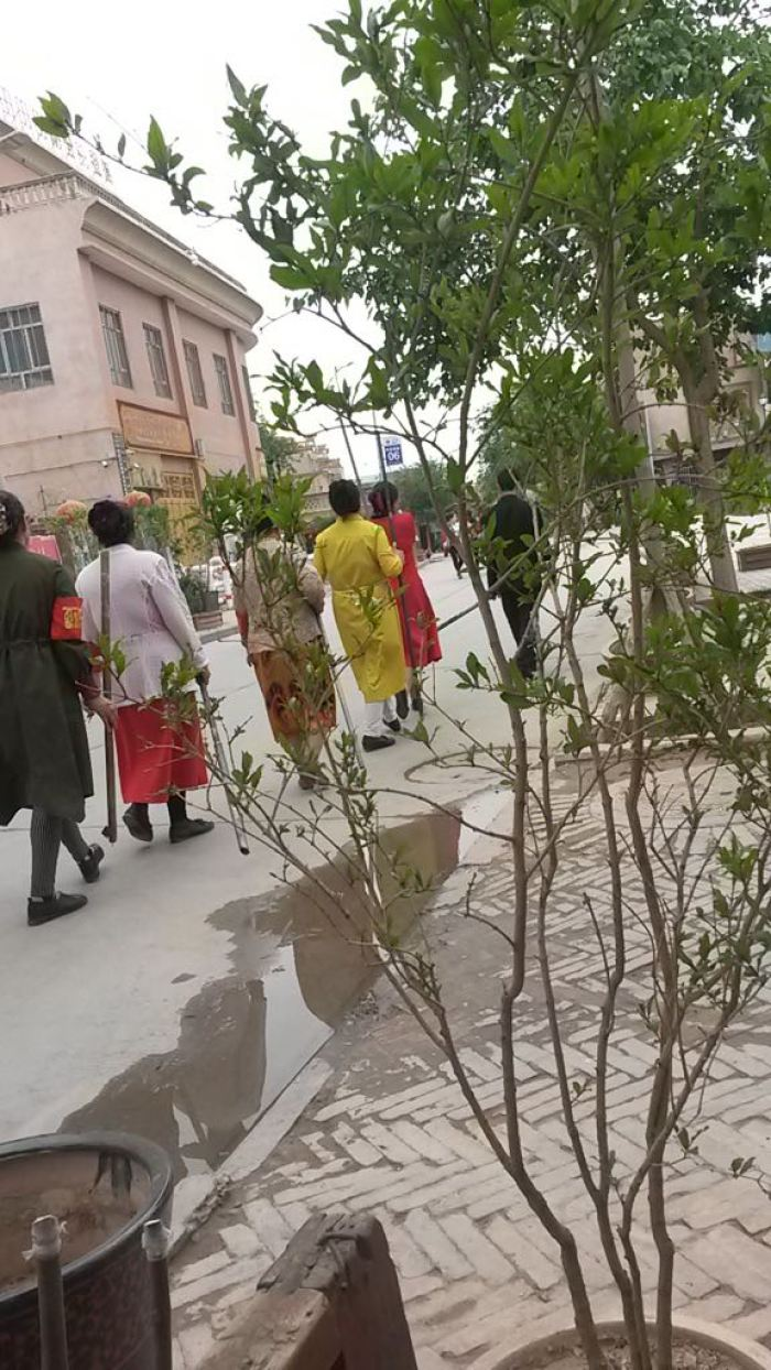 """Kashgar housewives acting as """"home guards"""" parading with clubs, sticks and home made weapons."""