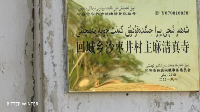 """This Jummah mosque is in Shazaojing village of the Huicheng township in Kumul. The crescent moon and star symbols on top of the mosque have all been removed, and tight wire netting has been attached to the surrounding walls. The notice at the entrance reads: """"Party members, state officials, and minors not allowed in religious establishments."""""""