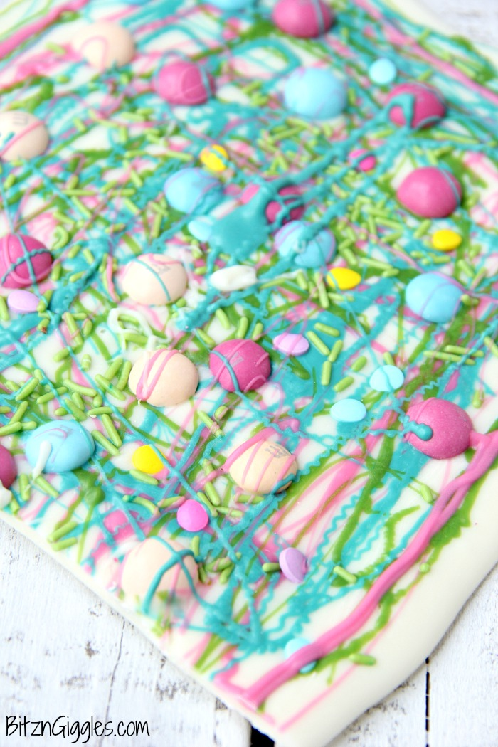 A fun twist on traditional candy bark with M&Ms, sprinkles and colored candy coating drizzle! Perfect for spring and Easter!