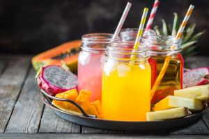 Glasses of tasty fresh tropical juices with fresh tropical fruits, Papaya Pine Apple Mango Dragon.