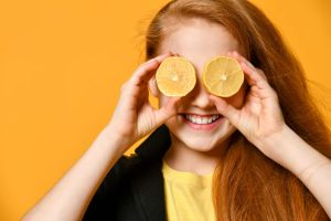 Schoolgirl in black jacket and yellow t-shirt. She is smiling, put two halves of lemon at her eyes, posing on orange background. Sincere emotions, fashion, beauty.