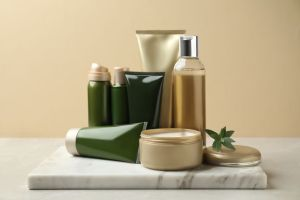 Different cosmetic products on white table against beige background.