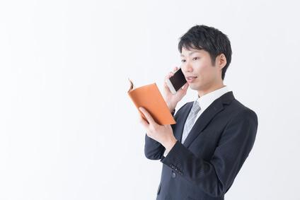 手帳と携帯電話を持っているスーツを着た男性