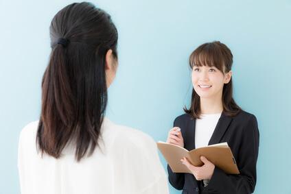 若い女性がメモをとりながら先輩の話を聞いている