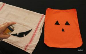 on colle la feutrine noire sur le tissu orange afin de donner au sac à bonbons d'Halloween son motif tête de citrouille
