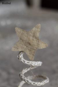 venir coller l'étoile de tissu doré au sommet du sapin marque place en tricotin