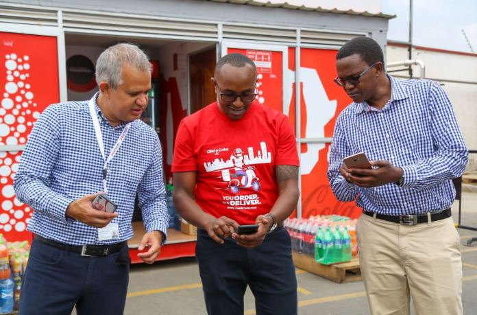 Franchise Director, Kenya and Tanzania, Oliver Soto (left), Coca-Cola Marketing Manager- Kenya, Evanson Ndung'u (middle) and Sales and Marketing Director - CCBA, Josphat Mwangi (right) attempt to make an order via DialACoke during the launch event at Nairobi bottlers offices in Embakasi - Bizna Kenya