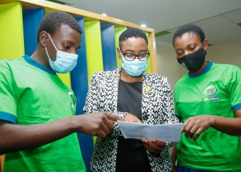 KCB Foundation Ag Chief of Party Caroline Wanjeri (center) reviews the KCSE results posted by Allan Wasonga Udoma (left) alongside Allan's mother Rose Auma Oloo (right). Allan emerged second nationally posting a straight-A during 2020 KSCE Examinations - Bizna Kenya