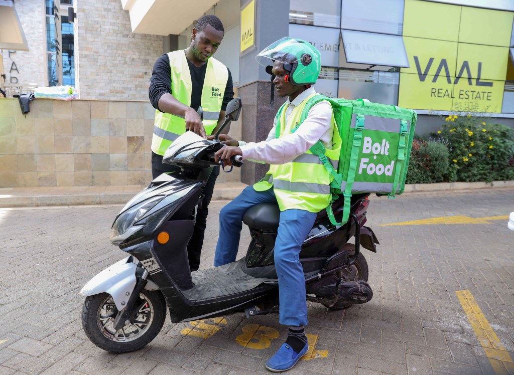 Edga Kipngetich, Bolt Food Country Manager (Left) with Daniel Karim Bolt Food courier go through the features of an electric bike during Bolt Ebike launch at their offices in Nairobi - Bizna Kenya