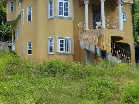 This 3 storey house sits on over 3 acres of land and is enclosed with concrete block walls and wire fencing