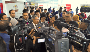 Media personnel crowd around Tok Pa and Kak Yasmin.