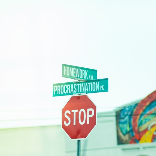 Image of a stop sign underneath a sign for Procrastination Road