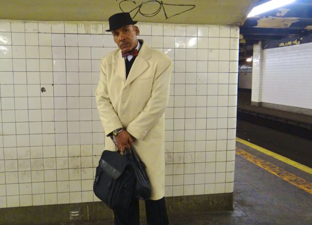 """This is Brother Rahmel. We spotted him waiting for the G train, dressed sharply in a white cashmere coat, complete with a red bow tie. """"I'm a Muslim,"""" he said proudly. """"I follow the teachings of the Honorable Minister Louis Farrakhan."""""""