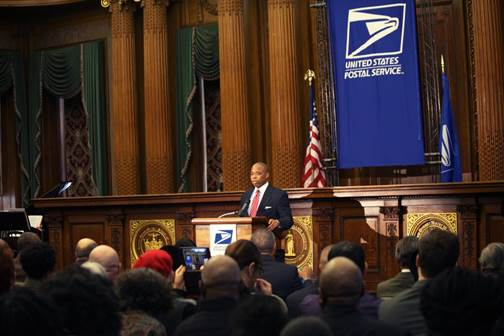 Brooklyn Borough President Eric Adams (left-center) commemorates the unveiling of the new United States Postal Service's Forever stamp in honor of Shirley Chisholm at a ceremony inside Brooklyn Borough Hall