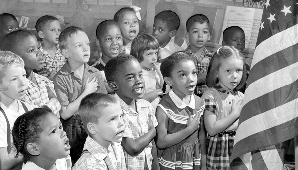 (A year after the Supreme Court's Brown vs. Board of Education ruling ended school segregation, first-graders recite the Pledge of Allegiance in 1955 at Gwynns Falls Elementary School.) [Source:Richard Stacks, Baltimore Sun]