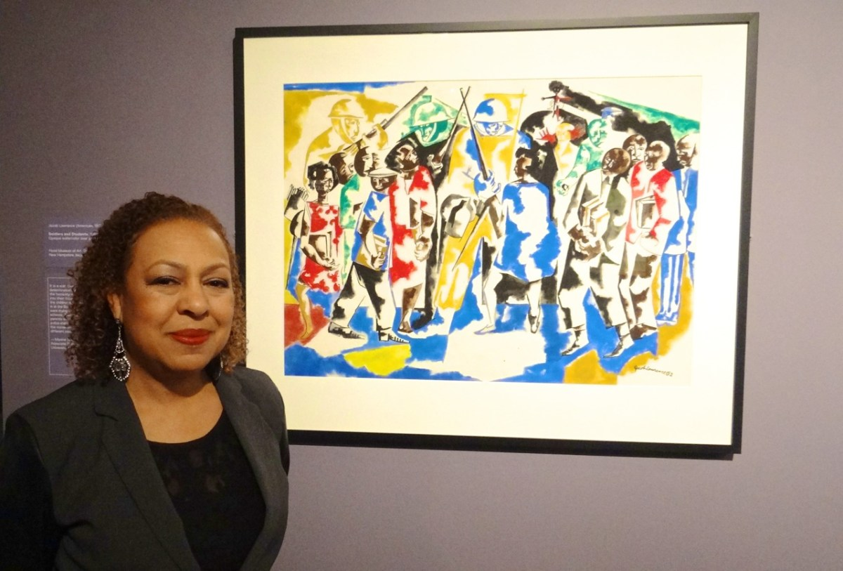 """""""Witness: Art and Civil Rights in the Sixties,"""" at the Brooklyn Museum. Kellie Jones, the exhibit's co-curator, stands next to Jacob Lawrence, Soldiers and Students, (1962). Opaque watercolor over graphite on wove paper. Hood Museum of Art, Dartmouth College, Hanover, New Hampshire. Bequest of Jay R. Wolf, class of 1951."""