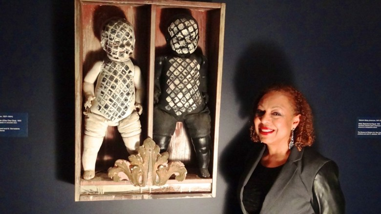 """""""Witness: Art and Civil Rights in the Sixties,"""" at the Brooklyn Museum. Co-curator Kellie Jones stands next to a piece by Edward Kienholz, It Takes Two to Integrate (Cha Cha Cha), (1961). Painted dolls, dried fish, glass in wooden box. Collection of David R. Packard and M. Bernadette Castor, Portola Valley, California."""