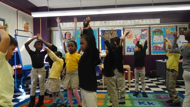Children stretch after story time at TFOA Professional Preparatory Charter School