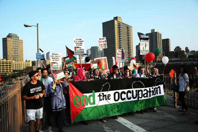 Cops are investigating the source of a giant flag in support of Palestine that was hung from the Manhattan Bridge