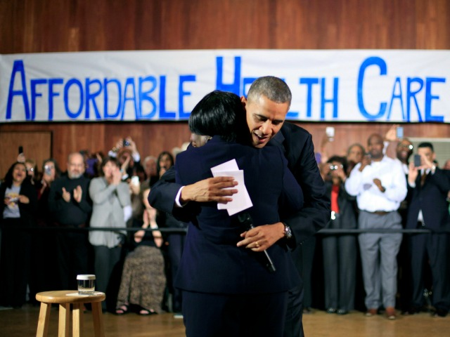 President Barack Obama hugs Edna Pemberton, who introduced him, before speaking with volunteers who helped people enroll through the HealthCare.gov site at Temple Emanu-El Wednesday, Nov. 6, 2013, in Dallas. Obama traveled to Texas to pitch health care and raise money for the Democratic party.