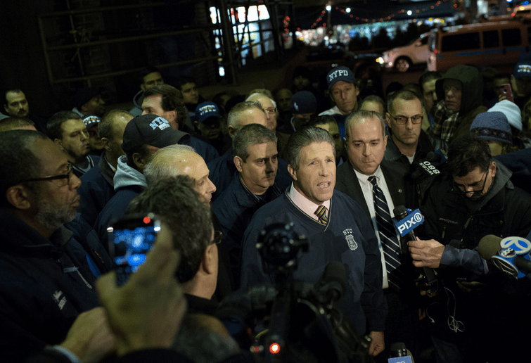 Patrick Lynch, president of the Patrolmen's Benevolent Association, addressing the media on Saturday outside the Woodhull Medical and Mental Health Center, where the two officers were taken after being sho