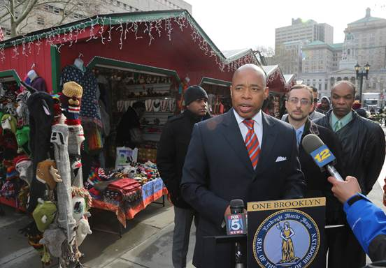 Brooklyn Borough President Eric L. Adams, joined by Brian McLaughlin, interim executive director of the Congress of Racial Equity (CORE) (2nd from right), launched the inaugural Holiday Market Village in Columbus Park.                                   Photo: Kathryn Kirk/Brooklyn BP's Office