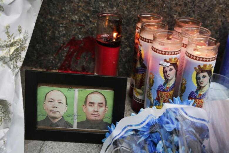Photos of the NYPD Officers Weinjen Liu (left) and Rafael Ramos are displayed at the Bed-Stuy memorial near where they were killed Saturday. Photos: Mark Lennihan/AP