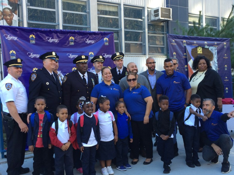 D.I. Chell, Assistant Chief Maddrey, Maritza Ramos, Jordan Durso, Pastor Ralph Castillo, and Principal Best pose with foundation members, officers from the 79th Precinct and students from P.S. 59