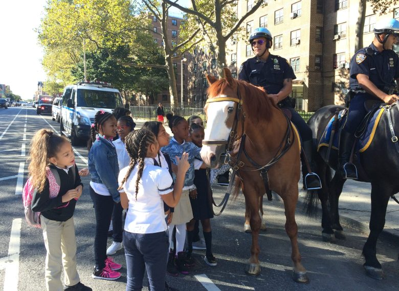 Students at Thursday's event pet a mounted police horse. A group of girls from P.S. 59 approach mounted police horse at backpack giveaway event.