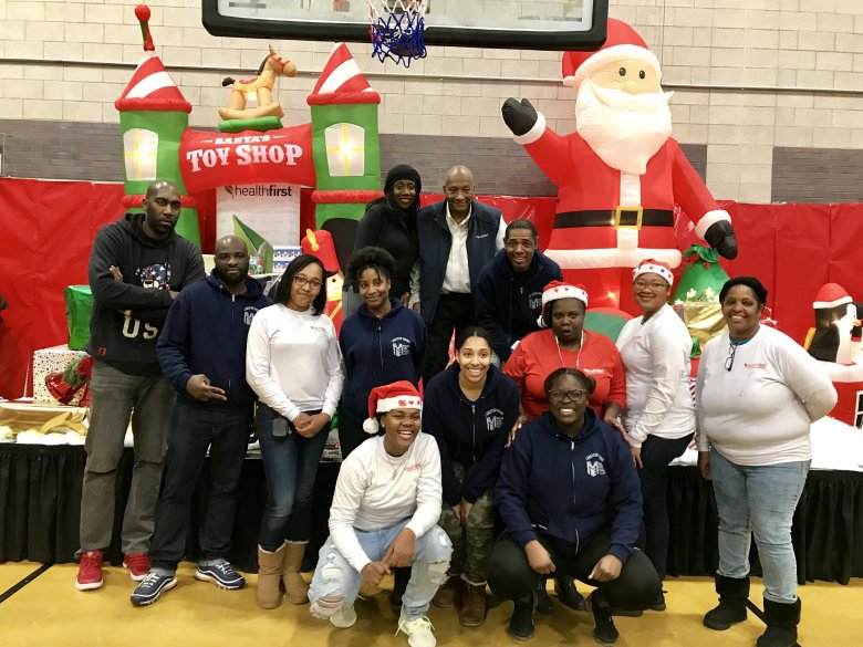 More than 60 HealthFirst employees and Brownsville residents came together to make the annual Toyland a truly cheerful experience for the Brownsville community. Photo credit: