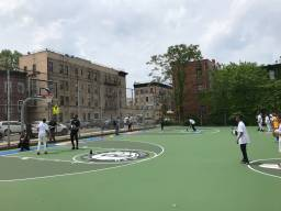 Kids play on the new basketball courts in Crown Heights by the playground