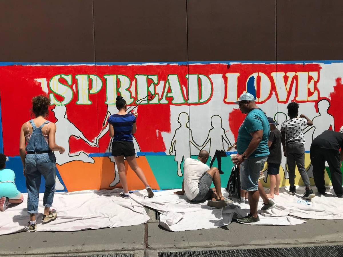 """Adults and kids help paint the """"Spread Love"""" community mural on Atlantic Terminal Center"""