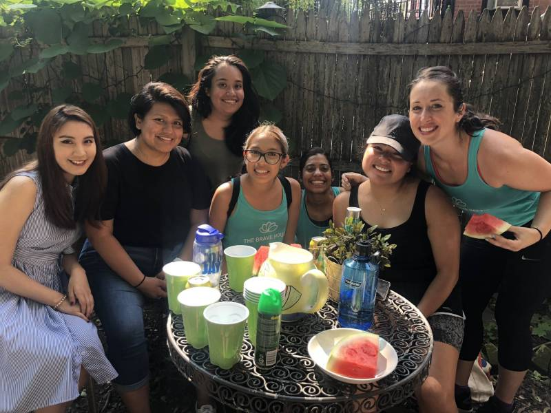 Brave House volunteers and community members eat watermelon after a cycling class.
