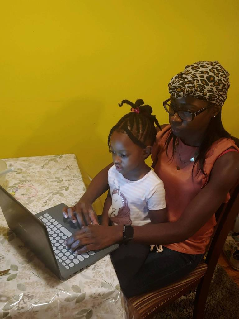 Mother helps her toddle with virtual learning classroom.