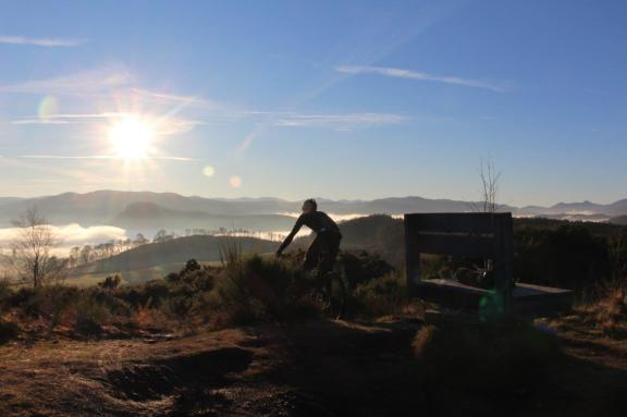 Mountain bikers in the 2017 Strathpuffer 24-hour mountain bike event ride into the sunset.